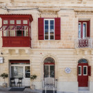 Façade with traditional Maltese balcony overlooking side sea views