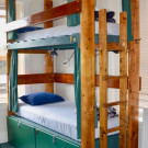 Wooden bunk bed with large green storage lockers underneath